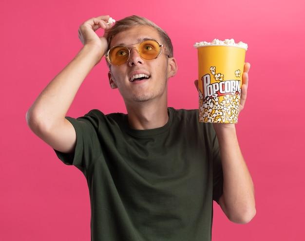 ポップコーンのバケツを保持し、ピンクの壁に分離された頭にポップコーンの部分を保持している緑のシャツと眼鏡を身に着けている若いハンサムな男を見て感動