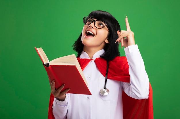 緑の壁に隔離された上で本のポイントを保持している眼鏡と医療ローブとマントと聴診器を身に着けている若いスーパーヒーローの女の子を見て感動