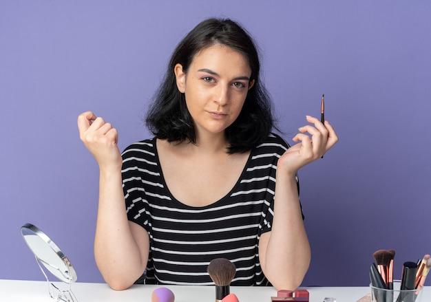 Впечатленная молодая красивая девушка сидит за столом с инструментами для макияжа, держа кисть для макияжа, изолированную на синей стене