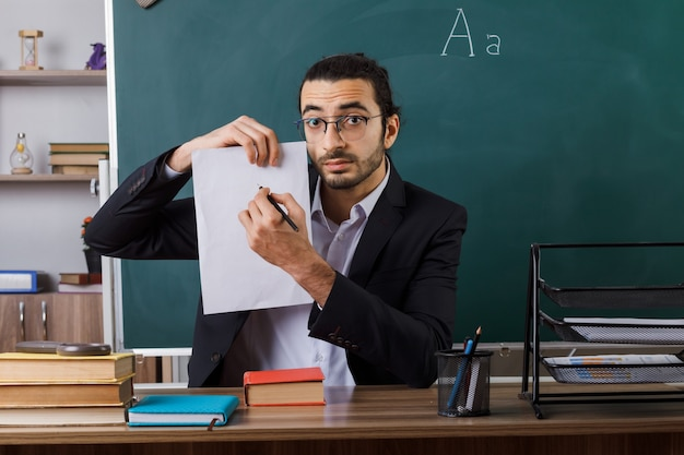 Impressed male teacher wearing glasses holding paper with pen sitting at table with school tools in classroom