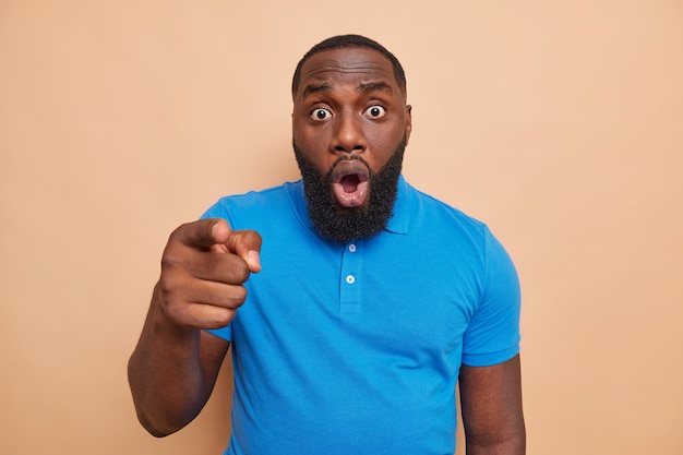 Impressed man points index finger at camera popping eyes from astonishment dressed in casual blue t shirt isolated over brown wall amazed by something