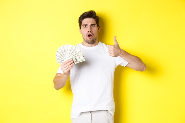 Impressed man showing thumb up, holding money credit, standing over yellow background.