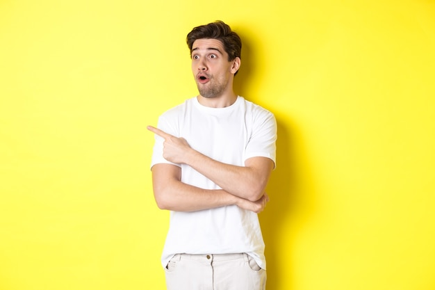 Impressed man in white t-shirt, looking and pointing finger left at promo, check out advertisement, standing against yellow background