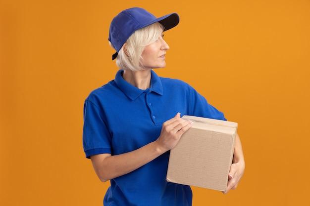 Donna di consegna bionda di mezza età impressionata in uniforme blu e cappuccio che tiene scatola di cartone guardando il lato isolato sulla parete arancione con spazio di copia