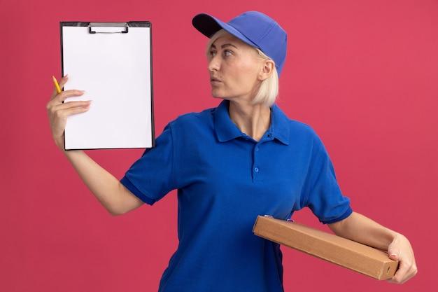 Donna di consegna bionda di mezza età impressionata in uniforme blu e cappuccio che tiene il pacchetto della pizza della matita degli appunti che esamina la lavagna per appunti isolata sulla parete rosa