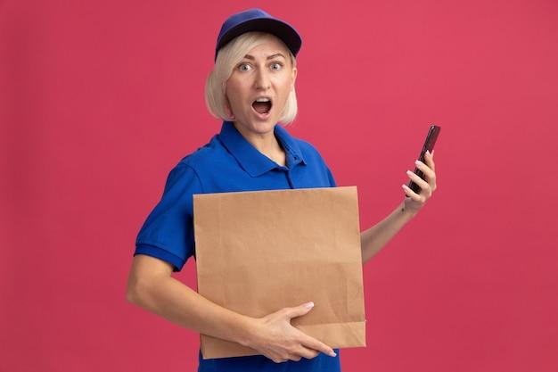 Donna bionda di mezza età impressionata in uniforme blu e berretto con pacchetto di carta e telefono cellulare isolato su parete rosa