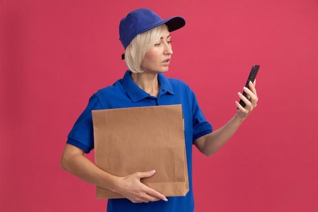 Donna di consegna bionda di mezza età impressionata in uniforme blu e cappuccio che tiene pacchetto di carta e telefono cellulare guardando il telefono isolato sulla parete rosa