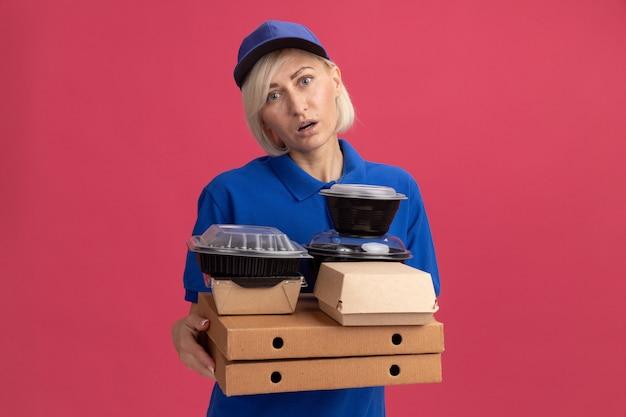 Impressionato donna bionda di mezza età consegna in uniforme blu e cappuccio che tiene pacchetti di pizza con contenitori per alimenti e pacchetto di carta alimentare su di loro guardando davanti