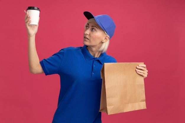Donna bionda di mezza età impressionata in uniforme blu e cappuccio che tiene una tazza di caffè in plastica e un pacchetto di carta che guarda la tazza di caffè