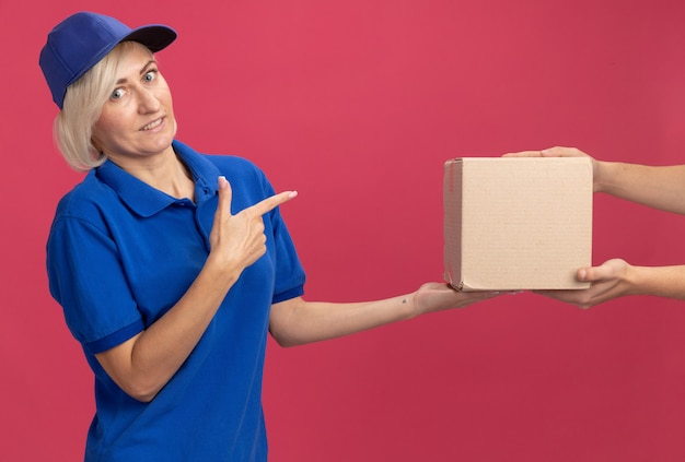 파란색 유니폼을 입은 중년 금발 배달 여성과 그것을 가리키는 고객에게 판지 상자를 주는 모자