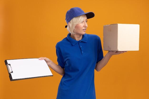 파란색 유니폼을 입고 카드박스와 클립보드를 들고 옆을 바라보는 모자를 쓴 중년 금발 배달 여성