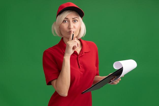 빨간 제복을 입은 중년 금발 배달부 여성이 연필과 클립보드를 들고 앞을 보고 복사 공간이 있는 녹색 벽에 격리된 침묵 제스처를 하고 있다