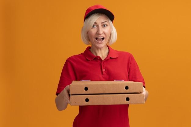 빨간 제복을 입은 중년 금발 배달 여성과 복사 공간이 있는 주황색 벽에 격리된 정면을 바라보는 피자 패키지를 들고 있는 모자