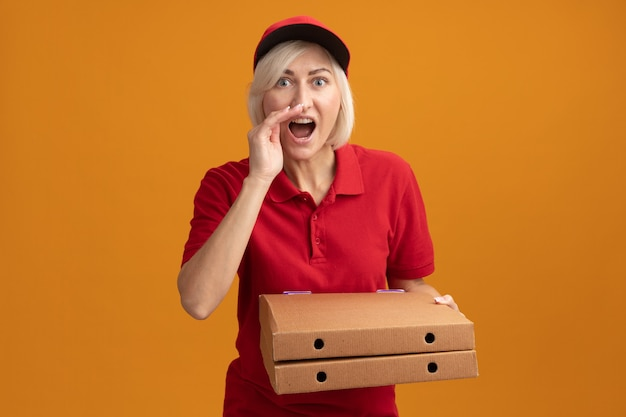 Impressionata donna bionda di mezza età in uniforme rossa e berretto che tiene i pacchetti di pizza tenendo la mano vicino alla bocca sussurrando