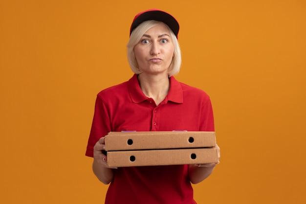 Donna di consegna bionda di mezza età impressionata in uniforme rossa e berretto che tiene i pacchetti di pizza guardando la parte anteriore isolata sulla parete arancione con spazio di copia