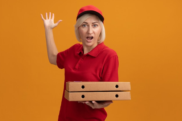Impressionata donna bionda di mezza età in uniforme rossa e berretto che tiene in mano pacchi di pizza alzando la mano