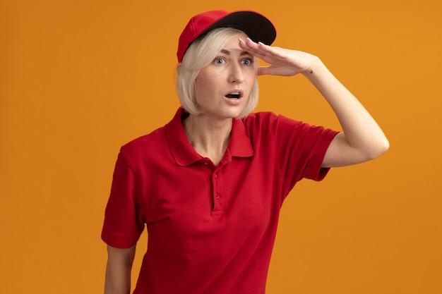 Impressionata donna bionda di mezza età in uniforme rossa e berretto che tiene la mano sulla fronte guardando di lato a distanza