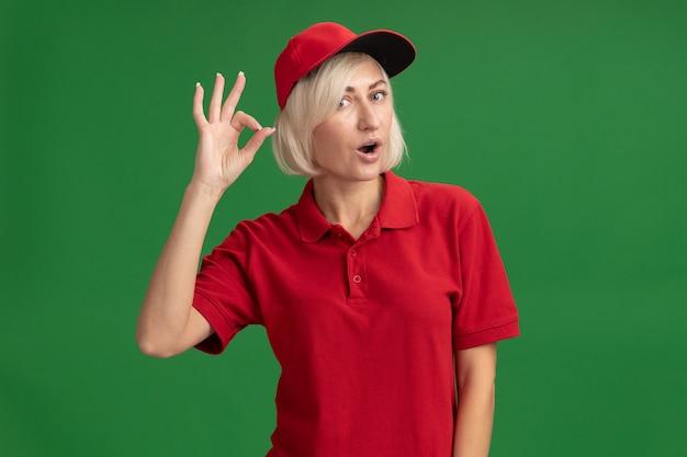 Donna di consegna bionda di mezza età impressionata in uniforme rossa e cappuccio che guarda davanti facendo segno giusto isolato sulla parete verde con lo spazio della copia