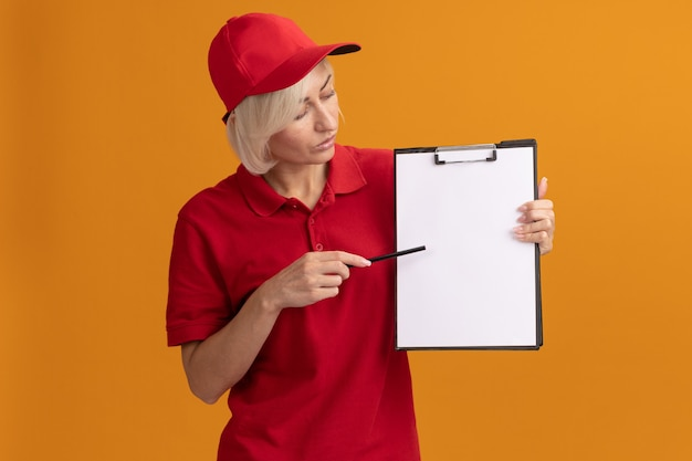 Donna di consegna bionda di mezza età impressionata in uniforme rossa e cappuccio che indica la lavagna per appunti con la matita che la esamina isolata sulla parete arancione con lo spazio della copia