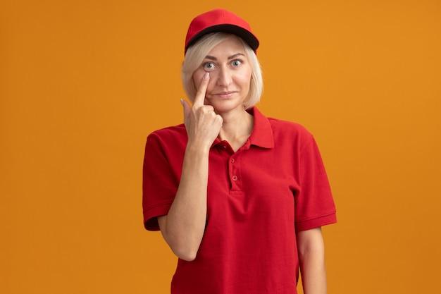 Impressionata donna bionda di mezza età in uniforme rossa e berretto che abbassa la palpebra