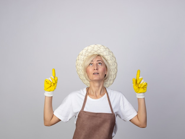 모자와 원예용 장갑을 끼고 보고 가리키는 제복을 입은 중년 금발 정원사 여성