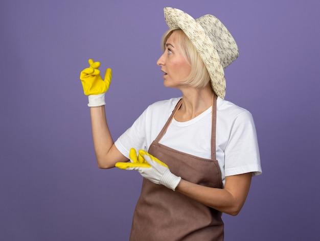 コピースペースで紫色の壁に隔離された後ろを指している側を見て帽子とガーデニング手袋を身に着けている制服を着た印象的な中年の金髪の庭師の女性