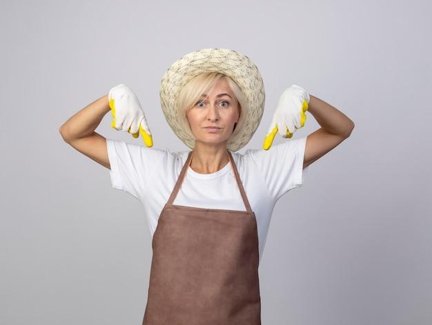 白い壁に隔離された下向きの帽子とガーデニング手袋を身に着けている制服を着た印象的な中年の金髪の庭師の女性