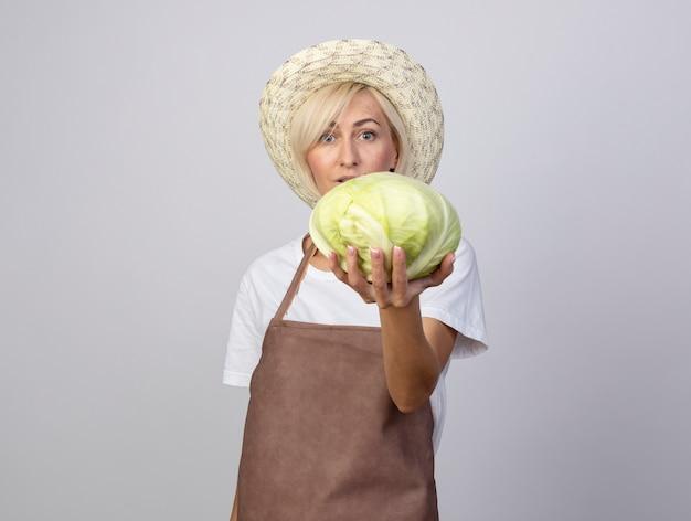 Впечатлила блондинка-садовница средних лет в униформе и шляпе, протягивая капусту