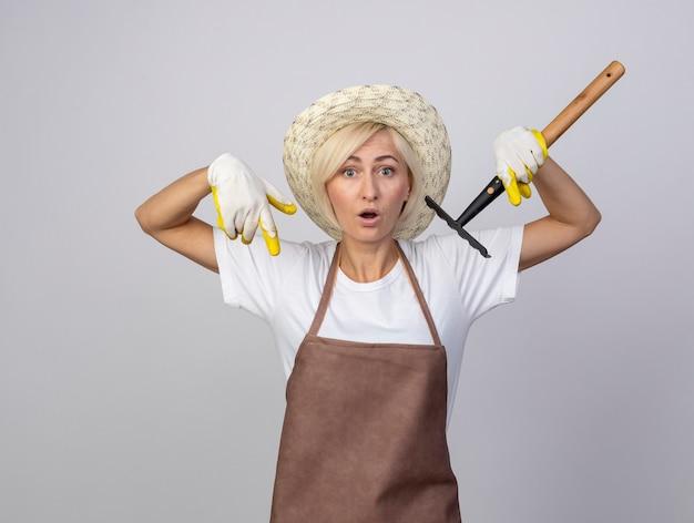 Donna bionda di mezza età impressionata del giardiniere in uniforme che indossa cappello e guanti da giardinaggio che tengono rastrello rivolto verso il basso