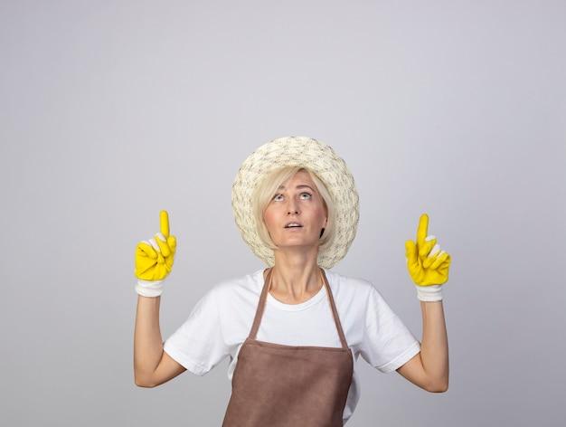 Donna bionda di mezza età impressionata del giardiniere in uniforme che indossa cappello e guanti da giardinaggio che guardano e puntano verso l'alto