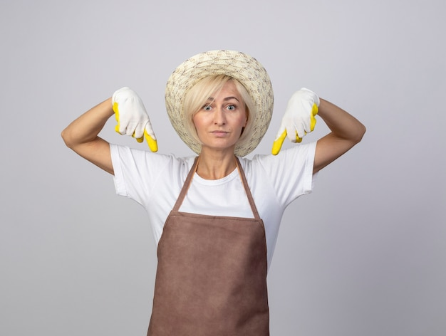 Impressed middle-aged blonde gardener woman in uniform wearing hat and gardening gloves  pointing down isolated on white wall