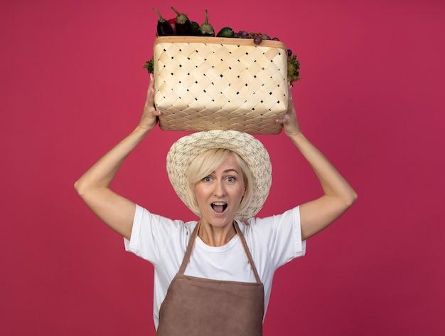 Donna bionda di mezza età impressionata del giardiniere in uniforme che indossa il cappello che tiene cesto di verdure sopra la testa isolata sulla parete cremisi