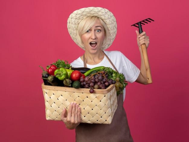 Donna bionda di mezza età impressionata del giardiniere in uniforme che indossa cappello che tiene cesto di verdure e rastrello isolato sul muro cremisi