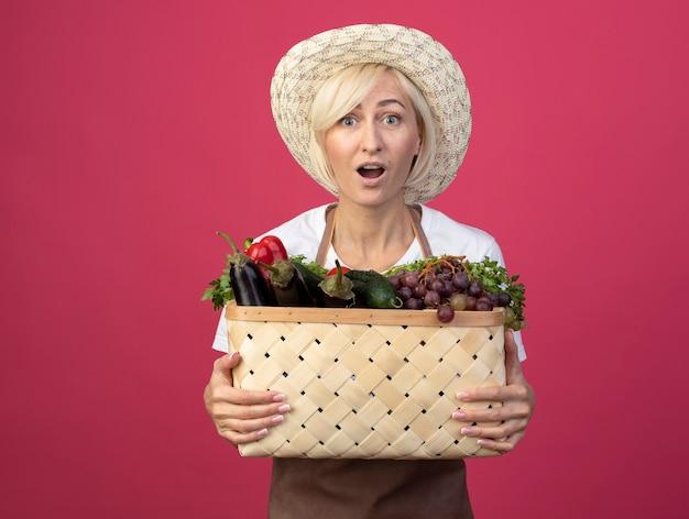 Donna bionda di mezza età impressionata del giardiniere in uniforme che indossa il cappello che tiene cesto di verdure