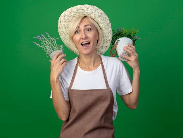 Impressed middle-aged blonde gardener woman in uniform wearing hat holding flowerpots near head looking at side isolated on green wall