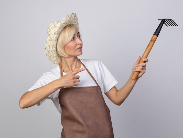 Donna bionda di mezza età impressionata del giardiniere in uniforme che indossa il cappello che tiene guardando e indicando il rastrello