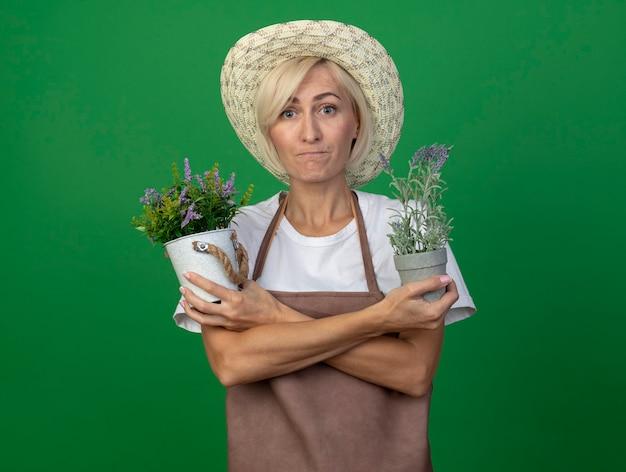Donna bionda di mezza età impressionata del giardiniere in uniforme che indossa il cappello che tiene le mani incrociate che tengono i vasi da fiori