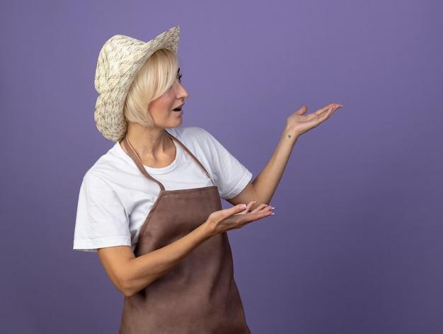 Donna bionda di mezza età impressionata del giardiniere in uniforme che indossa il cappello che guarda e che indica con le mani al lato