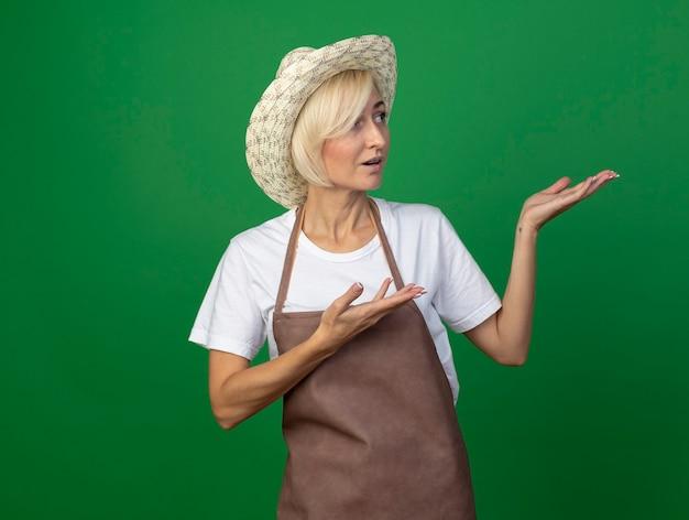 Donna bionda di mezza età impressionata del giardiniere in uniforme che indossa il cappello che guarda il lato che indica con le mani al lato