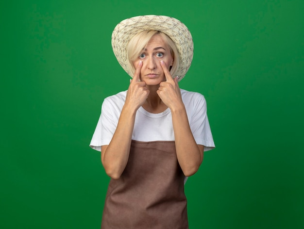 Impressed middle-aged blonde gardener woman in uniform wearing hat  pulling down eye lids isolated on green wall with copy space