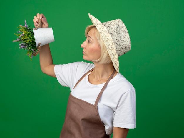 Donna bionda di mezza età impressionata del giardiniere in uniforme che indossa il cappello che alza il vaso di fiori su guardandolo isolato sulla parete verde con lo spazio della copia