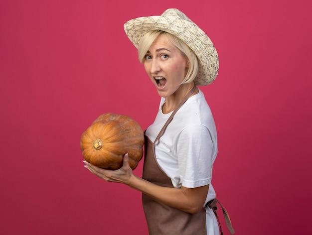 Donna bionda di mezza età impressionata del giardiniere in uniforme che indossa il cappello in piedi nella vista di profilo che tiene zucca butternut con la bocca aperta isolata sulla parete cremisi con lo spazio della copia