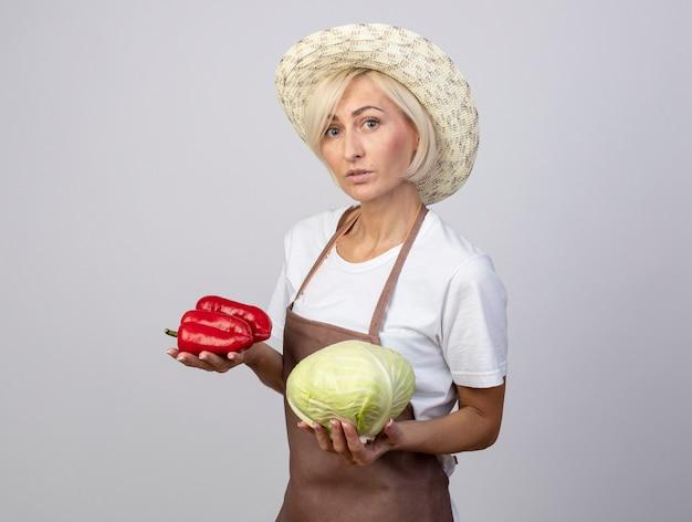 Donna bionda di mezza età impressionata del giardiniere in uniforme che indossa il cappello in piedi in vista di profilo che tiene peperoni e cavolo guardando la parte anteriore isolata sul muro bianco con spazio di copia