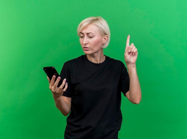 Impressionato donna di mezza età bionda slava che tiene e guardando il telefono cellulare che alza il dito isolato sulla parete verde con lo spazio della copia