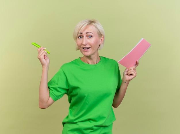 Впечатленная белокурая славянская женщина средних лет, держащая ручку и блокнот, смотрящую вперед, изолированную на оливково-зеленой стене