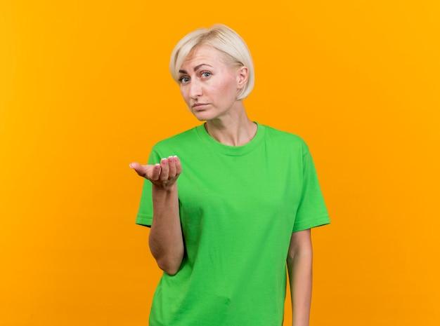 Donna slava bionda di mezza età impressionata che guarda davanti che mostra la mano vuota isolata sulla parete gialla con lo spazio della copia