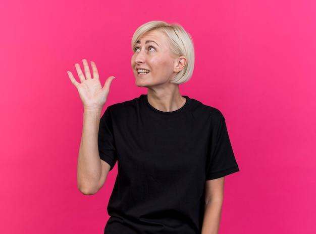 Donna slava bionda di mezza età colpita che guarda al lato che fa ciao gesto isolato sulla parete rosa con lo spazio della copia