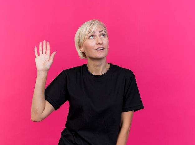 Donna slava bionda di mezza età impressionata che osserva in su facendo ciao gesto isolato sulla parete rosa con lo spazio della copia