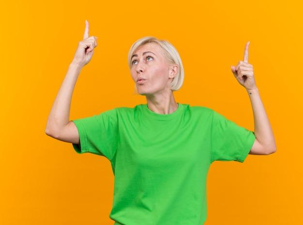 Впечатленная белокурая славянская женщина средних лет, указывая вверх, глядя на свой палец, изолированный на желтой стене