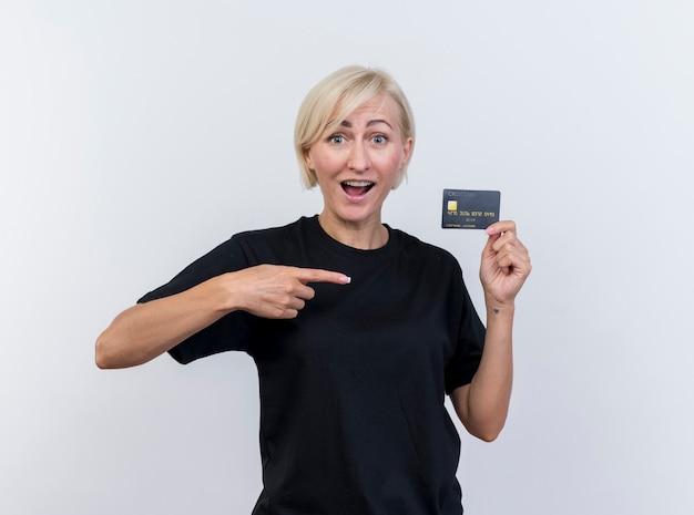 Impressionato donna slava bionda di mezza età che mostra la carta di credito che punta a esso guardando la telecamera isolata su sfondo bianco